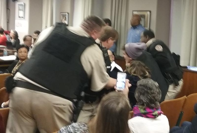Security attempt to remove protestors disrupting the Buffalo School Board meeting.