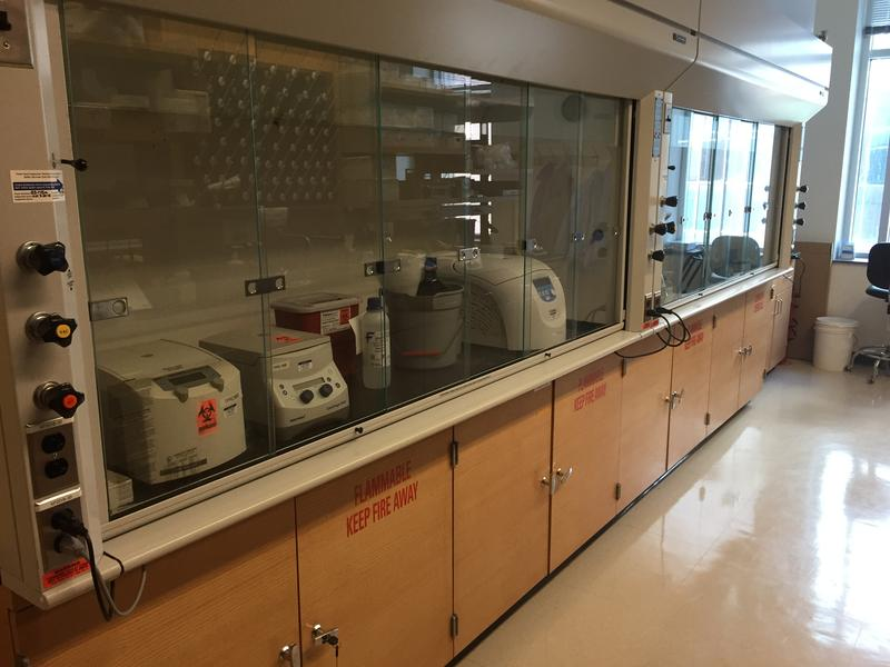 Centrifuges and other lab equipment sit inside protective hoods at the University at Buffalo HIV and HCV Clinical Pharmacology Laboratory