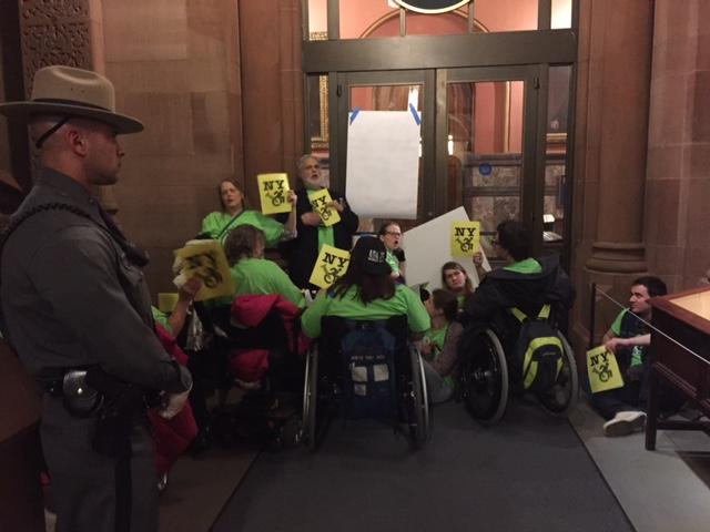 Protestors chant as they block the doors to offices at the state capitol