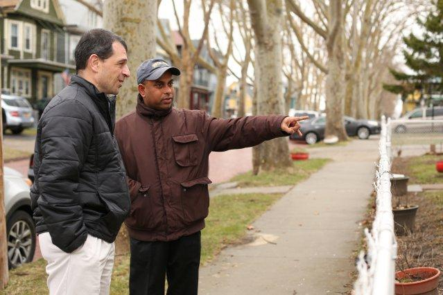 Chowdhury (R) stands with Tom Muscarella of the Erie County Health Department and points to improvements made to his lead-contaminated home.