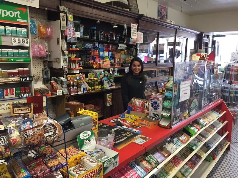 Brenda Mansour, whose father and uncle bought Mario's in 1986, stands near the tobacco displays. The woodwork behind her is some of what stood under the store's original owners, the family of founder Cesidio DiGregorio