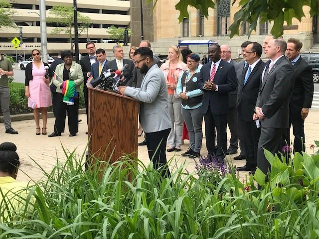 Pride Center Executive Director Damien Mordecai (at podium) is srrounded by elected officials kicking off Buffalo Pride Week.
