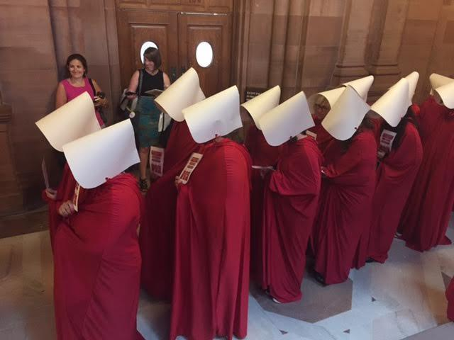 Abortion rights advocates dressed as handmaidens from the Margaret Atwood tale hold a silent protest Monday to call for passage of a reproductive rights bill in the state Senate.