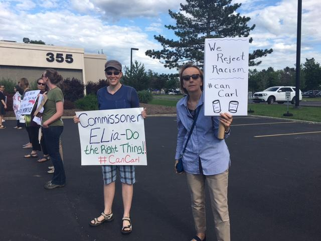 Protesters call on Commissioner Elia to removal Paladino.