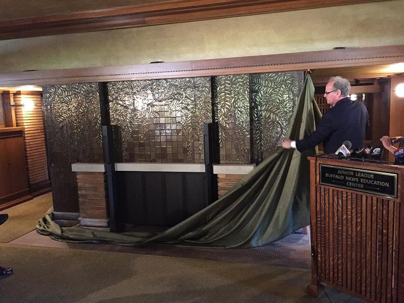 Howard Zemsky removes a curtain to reveal a wisteria mosaic fireplace inside the Darwin Martin House in Buffalo.