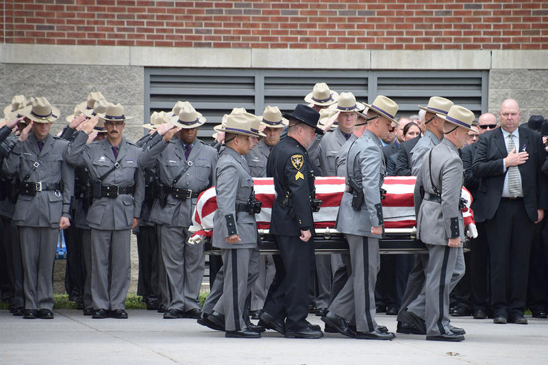 Honor guard salutes the passing coffin of New York State Trooper Joel Davis following the service.