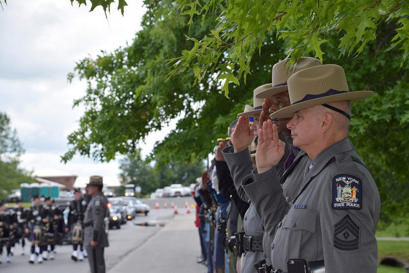 Law enforcement officials greet the funeral procession.