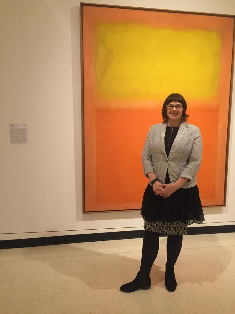 "Albright-Knox curator Holly Hughes standing in front of Mark Rothko's ""Orange and Yellow"""