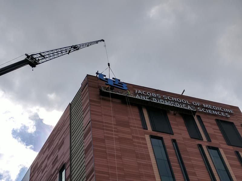 Construction workers connect the UB logo to the side of the new Jacobs School of Medicine and Biomedical Sciences.
