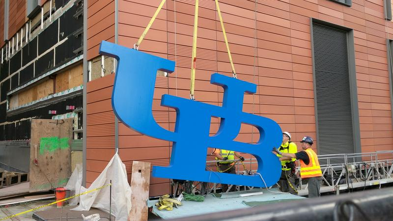 Construction workers guide the 800 pound UB logo upward from a trailer bed with lifting straps and the cable from a large crane.