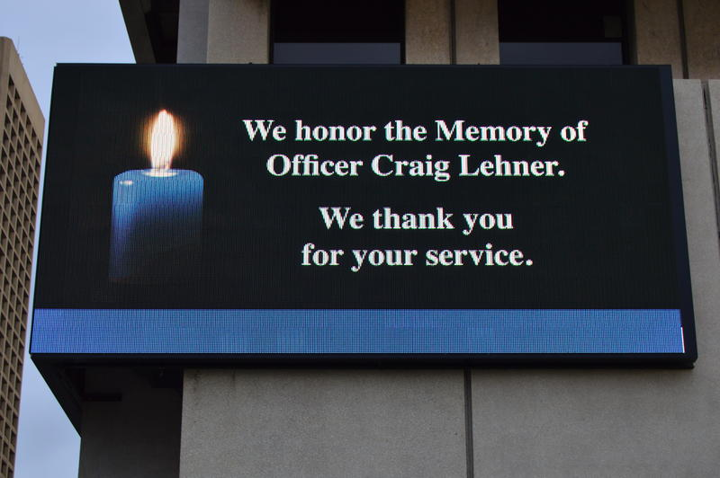 Signs, like this one on the side of The Buffalo News building, honored Craig Lehner on the day of his funeral