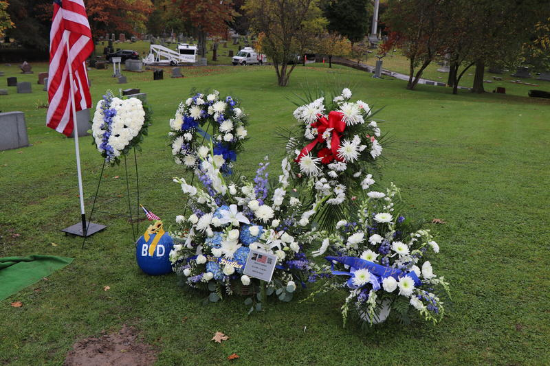 Wreaths, bouquets, and a small plaque adorned the graveside of Craig Lehner