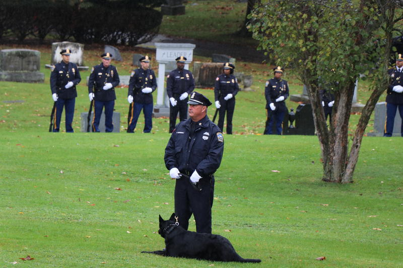 Members of a ceremonial firing squad and members of the Buffalo Police Department's K-9 Unit await the arrival of Craig Lehner's funeral procession