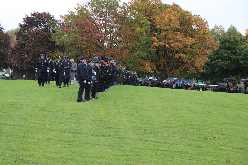 With the casket of Craig Lehner waiting, scores of law enforcement officers begin to line up on the field next to his grave for a final farewell