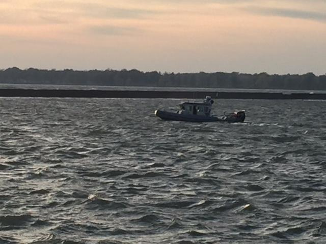 A boat drifts by in the swift waters of the Niagara River where Officer Craig Lehner died, while members of the Jeep Wrangler Club of Western New York gathered nearby for a vigil in his honor