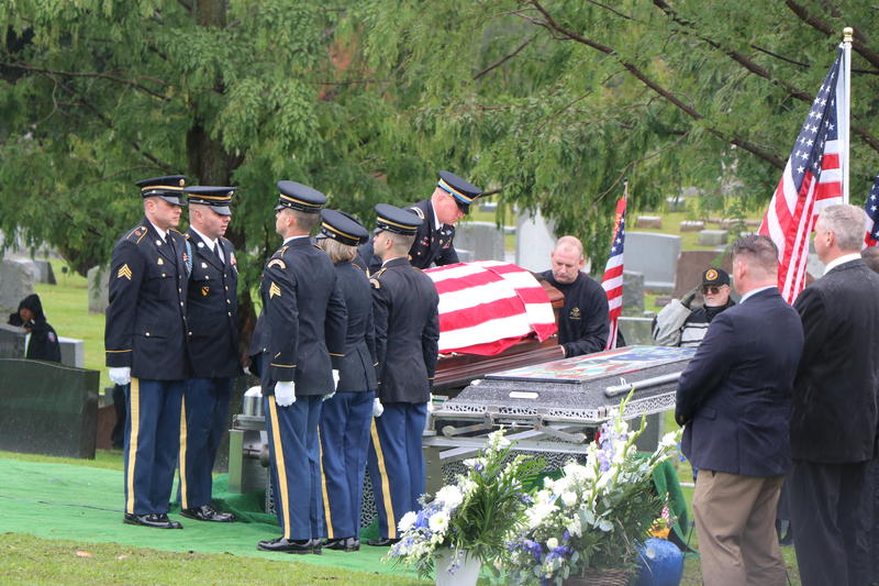 Members of an Army Honor Guard standby as one of their officers prepares the casket of Craig Lehner for burial