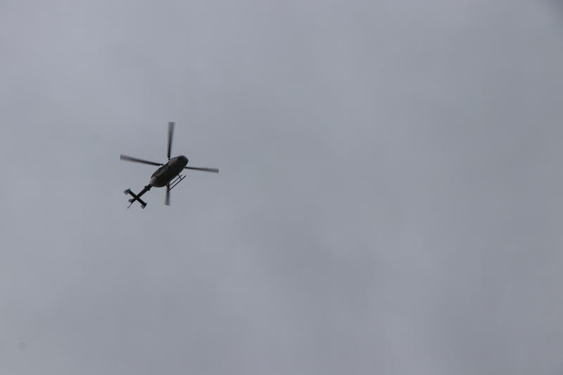 A helicopter conducts a flyover as part of the military and police traditions of sending off one of their own