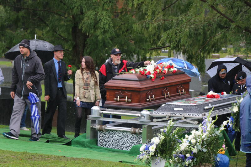 Family and friends of Craig Lehner place carnations and roses on his casket in a final farewell