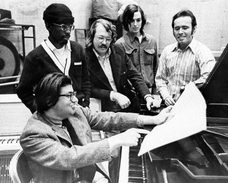 Morton Feldman, director of the Center of the Creative and Performing Arts, seated at piano surrounded by Creative Associates.