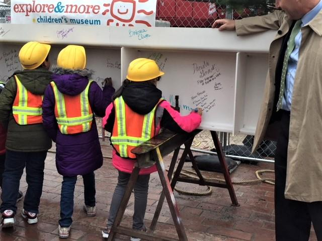 Hard-hat wearing kids scrawled their signatures on the final steel beam.