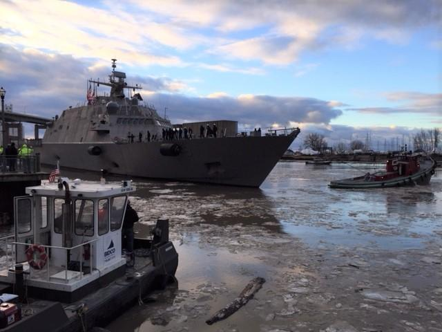 LCS-9 was guided out of the harbor by several boats.