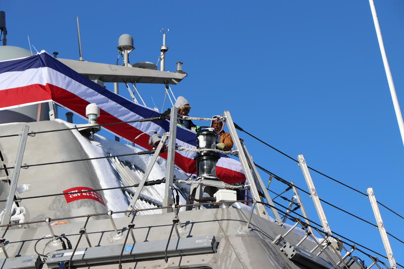Workers attach bunting to the rails of the new USS Little Rock in preparation for its commissioning ceremony in Buffalo.