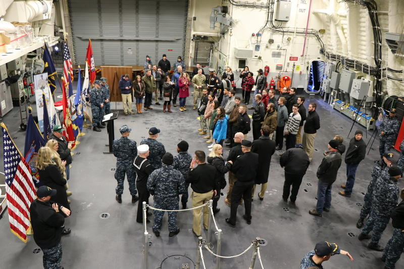 Members of the military, new enlistees, and family members gather inside the new USS Little Rock for an enlistment ceremony.