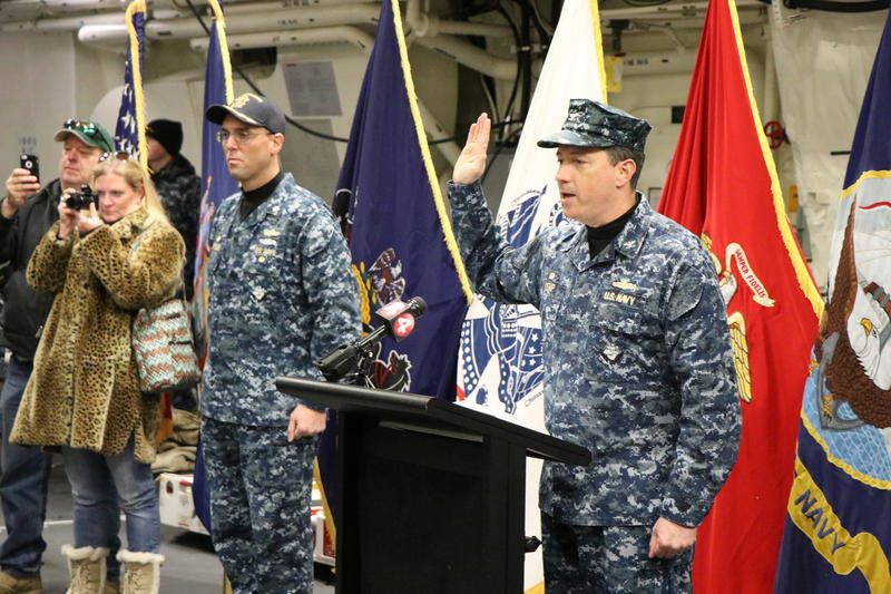 Captain David Kemp, Commander of U.S. Military Entrance Processing Command, recites the oath of enlistement to 18 Western New Yorkers as they join the armed forces.