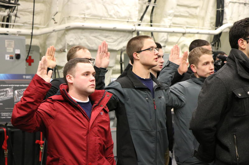 18 Western New Yorkers recite the oath of enlistement as they join the armed forces aboard the new USS Little Rock.