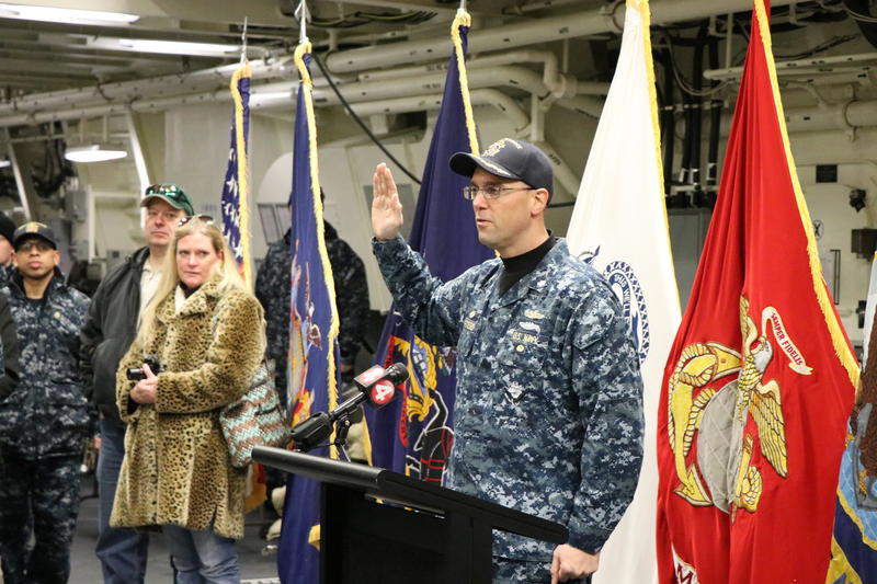 Commander Todd Peters, Commanding Officer of the new USS Little Rock, recites the oath of enlistement to 18 Western New Yorkers as they join the armed forces.