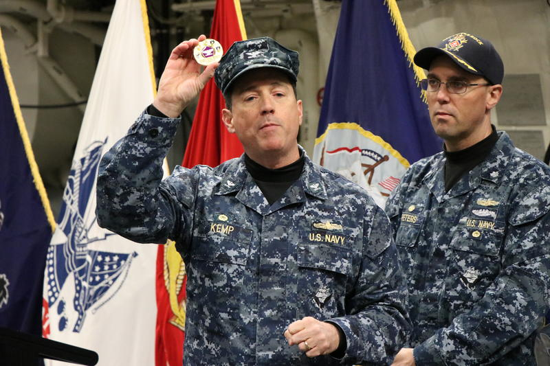 Captain David Kemp, Commander of U.S. Military Entrance Processing Command, holds up the ceremonial challenge coin of his command.