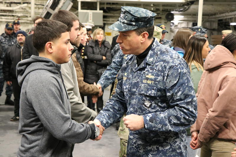 Captain David Kemp, Commander of U.S. Military Entrance Processing Command, presents the ceremonial challenge coin of his command to one of the 18 new enlistees who joined the armed forces aboard the new USS Little Rock.