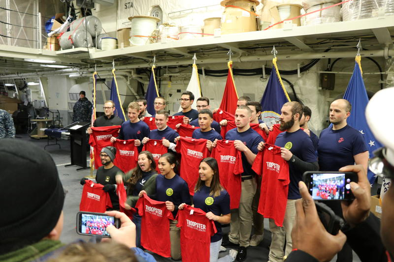 18 new enlistees who joined the armed forces aboard the new USS Little Rock smile for pictures in front of friends and family.