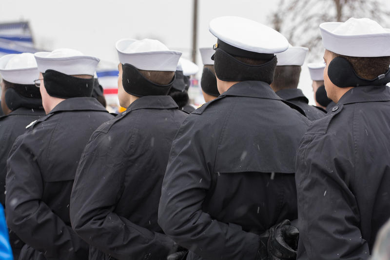Sailors in dress uniform stand at parade rest during the commissioning ceremony, keeping warm with ear muffs.