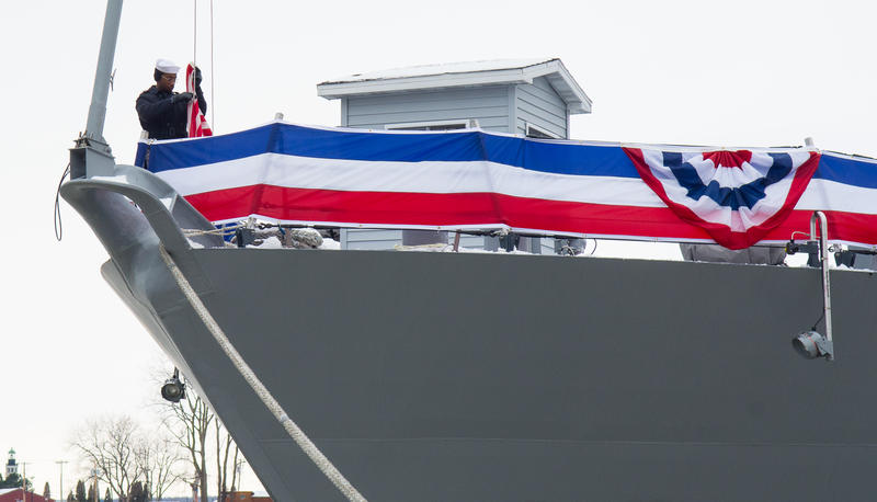A sailor removes an American flag flying from the bow of the ship and then folds it neatly into a triangle.