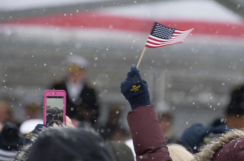 An excited guest waves a small American flag, wearing commemorative gloves for the commissioning of the new USS Little Rock.