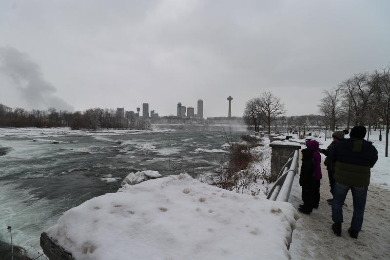 Visitors walk along the edge of the Niagara River.