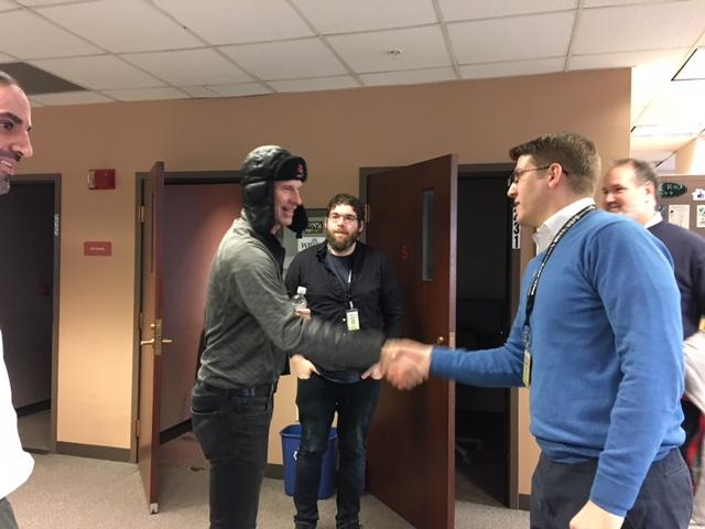 Former Buffalo Sabres goalie shakes hands with WBFO's Avery Schneider with WBFO's news team, Omar Fetouh, Nick Lippa and Michael Mroziak.