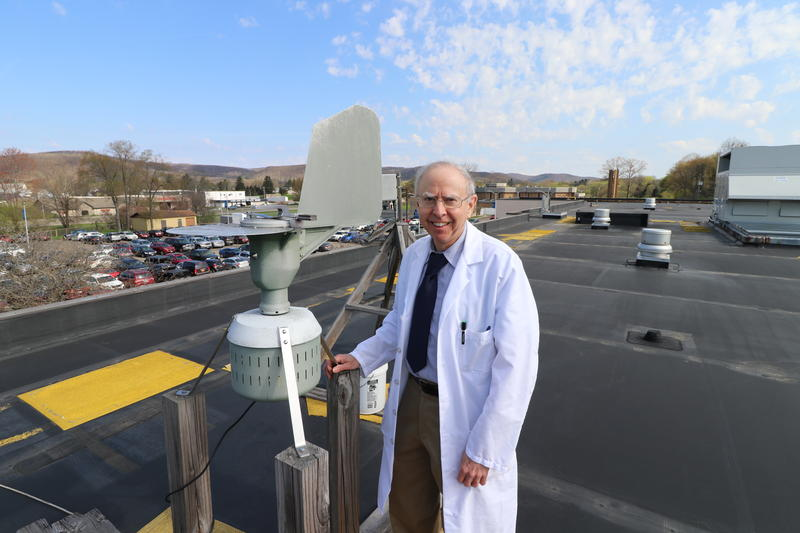 Dr. Fred Lewis poses for a picture with the Burkard air sampler. A wind-vane-like tail keeps the machine oriented into the wind, so it's got the best chance of sucking in particles.
