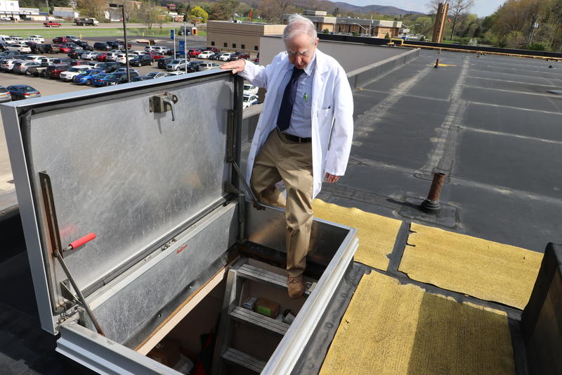 Fred Lewis begins to climb down from the roof of the Olean Medical Group Olean Medical Center, where he collects samples of pollen and mold.