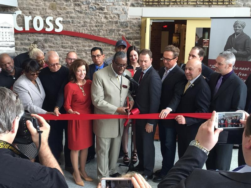 Numerous elected officials, tourism leaders, Niagara Falls Underground Railroad Heritage Center board members and other invited guests gather to cut the ceremonial ribbon marking the grand opening of the center.