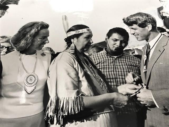 "Ethel Kennedy looks on as Seneca Wolf Clan Mother Lovina Logan presents RFK  beaded necklace after he was adopted into the tribe, and given the name ""Top of the Crowd"", 1968"