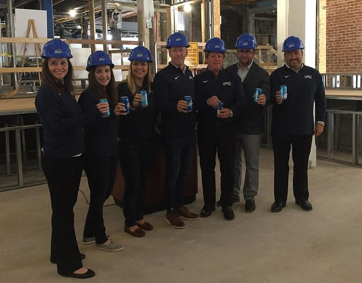 """Labatt USA and Pegula Sports and Entertainment representatives say """"cheers"""" following a progress report on the construction of the future Labatt House in Buffalo's Cobblestone District, adjacent to KeyBank Center."""