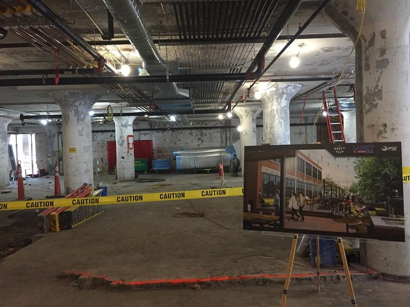 What will be the Draft Room restaurant remains under construction in the background, while a rendering on the easel shows what a beer garden on the grounds will look like when it opens in November.