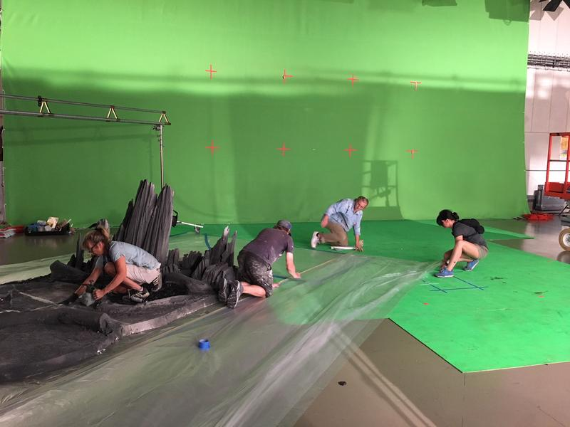 Crew members prepare to a shoot a scene in front of green screen