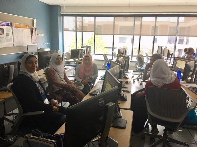 Female immigrant and refugee students attend computer class.