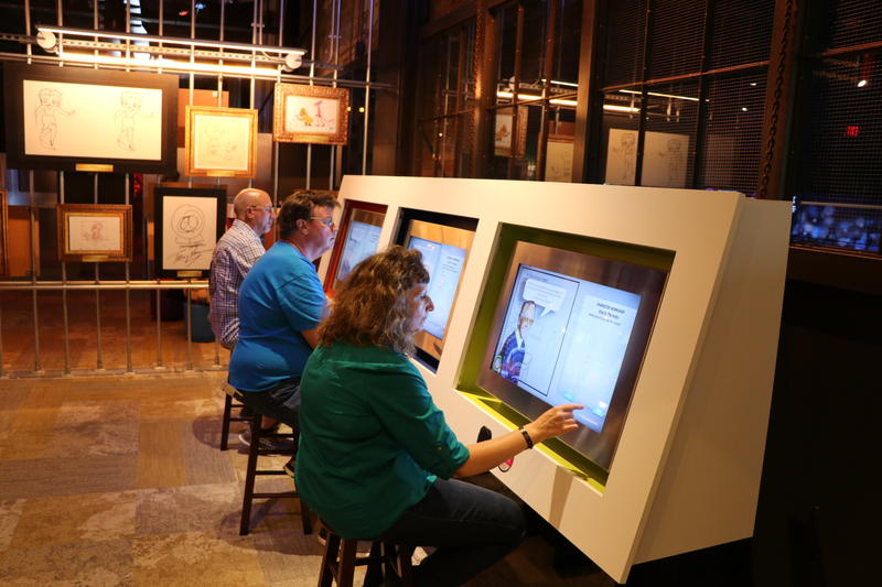 Visitors interact with touch-screen displays