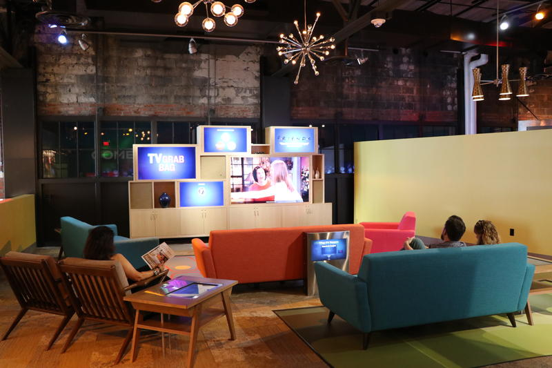 Visitors watch TV sitcoms in the living room lounge