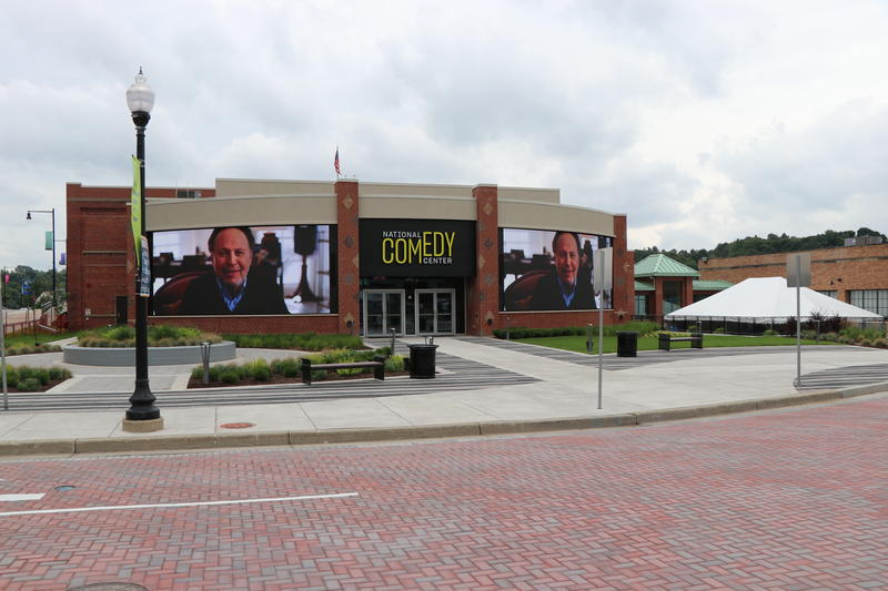 Messages from Billy Crystal and more than a dozen other comedians play on the screens outside the National Comedy Center