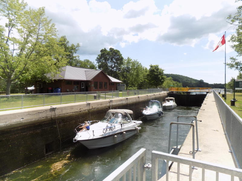 Upboand boats between the gates of Lock 6 in Frankford. The area between the gates is filling with water to lift the boats up to the proper level so they can exit.